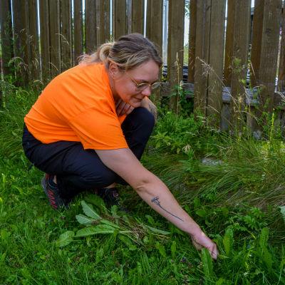 En kvinna i orange tröja sitter på huk och rensar ogräs.