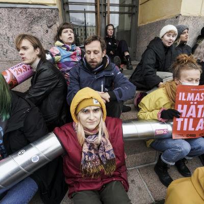 Elokapina-aktivister sitter vid statsrådets byggnad.