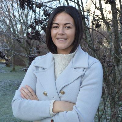 Ung kvinna i ljusblå vinterkappa med krage tittar in i kameran och ler.