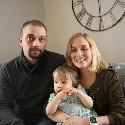 Ett ungt par sitter i en soffa. Kvinnan håller en liten flicka i famnen.