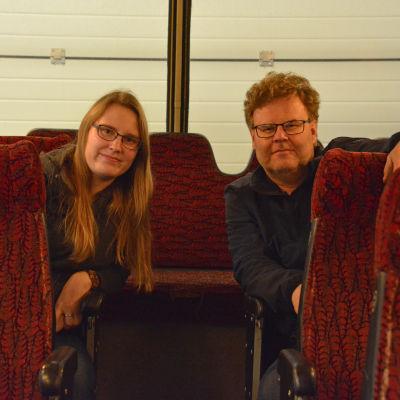 En kvinna och en man som sitter på varsinn sida om en bussgång.