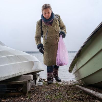 Nainen kerää roskia rannalla soutuveneiden välissä.