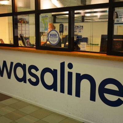 En person med munskydd sitter i Wasalines check in.