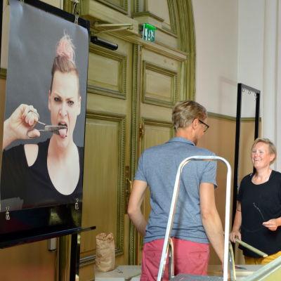 Ilar Gunilla Persson hänger upp sina fotografier i Lovisa kyrka
