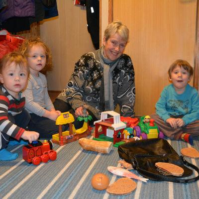Kvinna sitter på golvet tillsammans med barn och lite leksaker.