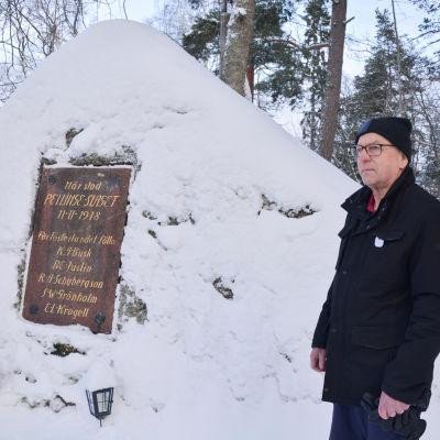 en fundersam erik liljeström framför den snötäckta minnesstenen över pellingeslaget