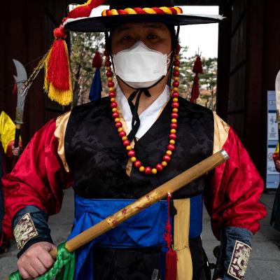 Perinneasuihin pukeutuneet vartijat kasvoillaan hengityssuojat.