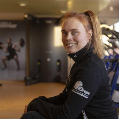 Ladylinen personal trainer Niiki Alakärppä henkilökuvassa. Ladylinen kuntosalin spinning-sali taustalla.