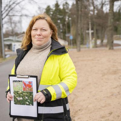 Raseborgs ansvariga parkchef Maria Eriksson poserar vid en väg med en bild i handen.