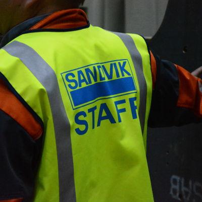 """Ryggen av en man med en skyddsväst där det står """"Sandvik staff"""" på."""
