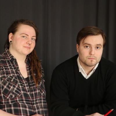 En ung kvinna med långt rödbrunt hår står bredvid en ung man som lutar sig mot ett bord.