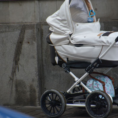 En vit barnvagn med betong i bakgrunden.