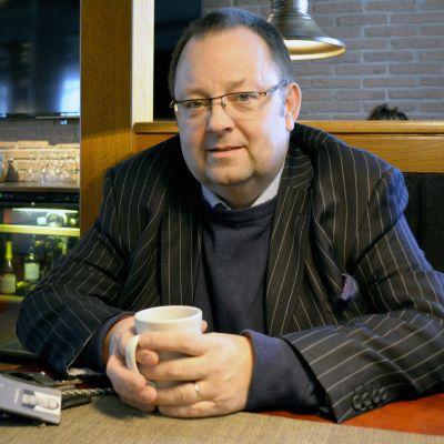 Carl Wideman istuu kahvilassa ja katsoo kameraan.