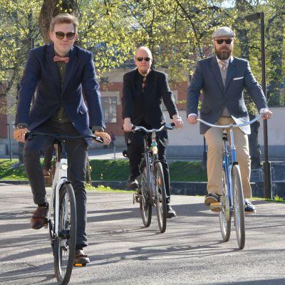 Miehet pyöräilevät pikkutakit päällä