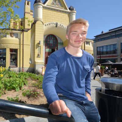 Jalkapalloilija Ilmari Niskanen istuu Kauppahallin edessä.