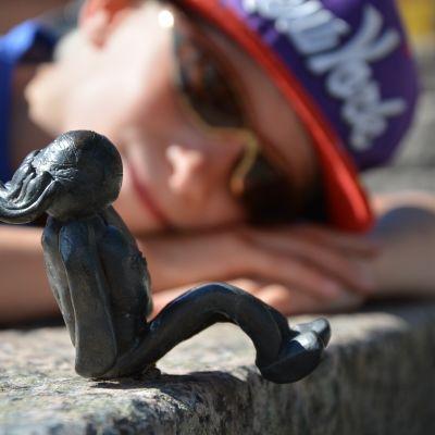 Lapsi ihastelee Piiloleikki-teoksen patsasta.