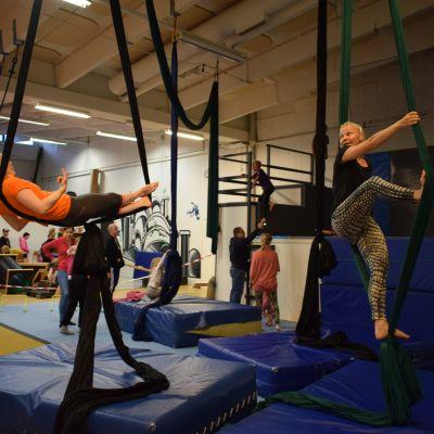 Kaisa Piesanen opastaa avointen ovien päivän kävijöitä keinumaan selällään ilma-akrobatia kankaassa Jyväskylän Sirkuskoulussa.