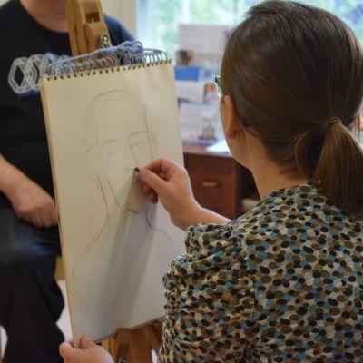 Iana Vulpe piirtää mallina toimivaa Tapani Paleniusta paperille Säynätsalon päiväkeskuksessa.