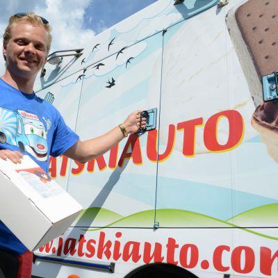 Jäätelömyyjä esittelee jäätelöpakettia auton vieressä.