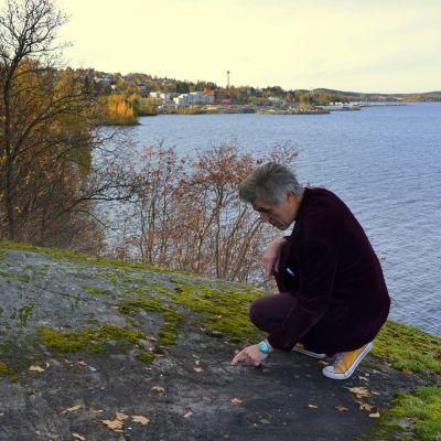 Antti Liuttunen kyykkii Onkiniemen kalliolla