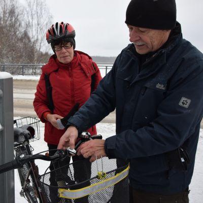 Veijo Kuosa asentaa etuvaloa Raili Järvelän pyörään.