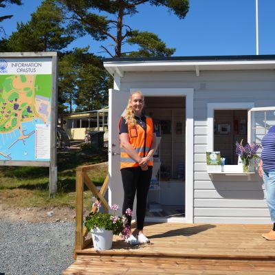 Två personer tar emot utanför en turistinfo kiosk.