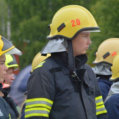 Två deltagare med gula hjälmar på brandkårslägret i Lovisa.