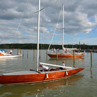 En klassisk segelbår förtöjd vid en brygga.