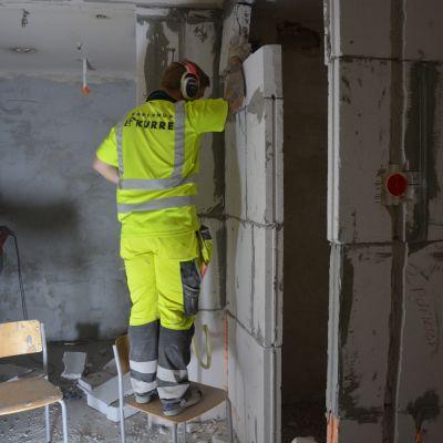 Byggarbetare står på en stol och murar en vägg.