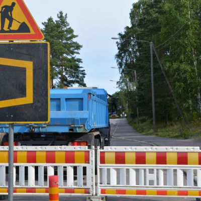 Vägskyltar om vägarbete, avspärrningsstaket och en blå lastbil.