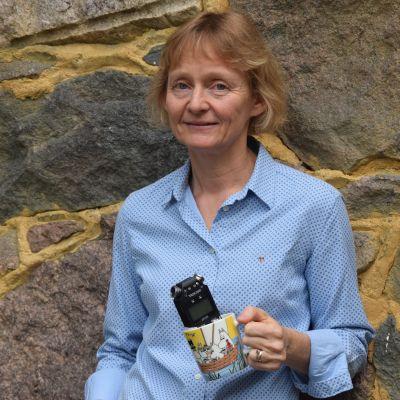 kvinna vid stenvägg med mugg