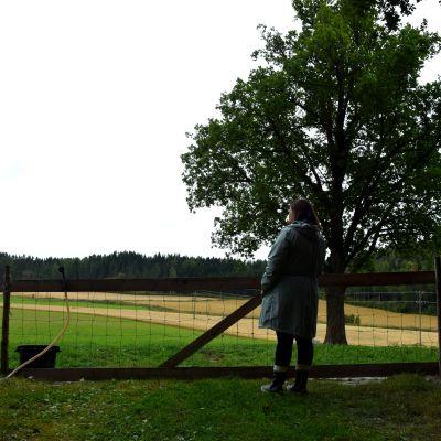 Maria Damén i siluett bakifrån utanför en fårhage.