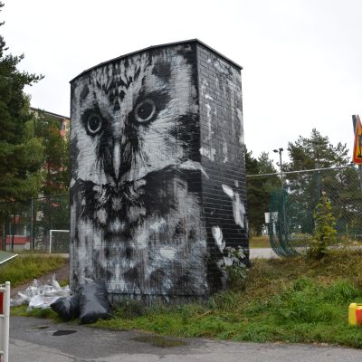 Stor målning av en uggla på en stor vägg.