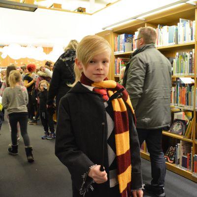 Bild på Aron Eklund, som står med halsduk, kåpa och trollstav på Harry Potter- evenemang.
