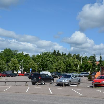 Bilar parkerade vid parkeringsrutor en sommardag. I bakgrnden träd och en vit byggnad. Till höger röda byggnader.