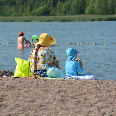 En kvinna och ett barn som sitter på en strand.