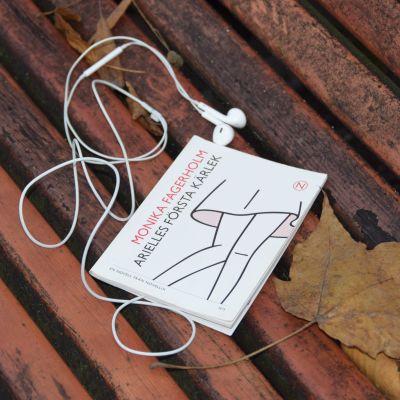"""Novellen """"Arielles första kärlek"""" omgiven av hörlurar."""