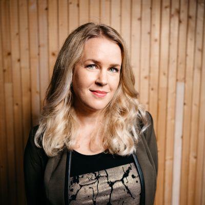 Hannah Norrena står inomhus mot en trävägg