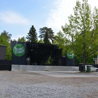 En konsertscen på en grusplan med ett träd i förgrunden.