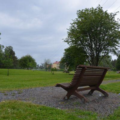 En parkbänk bredvid en grusgång på en gräsmatta.