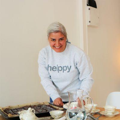 Hemvårdaren Jennifer Hanner dukar fram kaffekoppar och mockarutor och ler mot kameran.