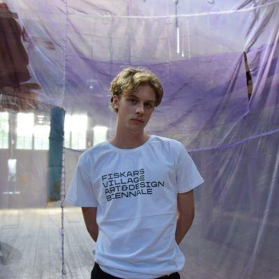 Max Aiha står framför konstverk på Fiskars Biennalen.