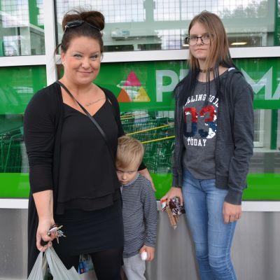 Mamma med två barn och matkasse utanför stormarket.