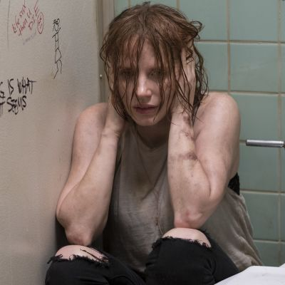 Beverly sitter hopkurad i ett toalettbås med händerna för öronen.