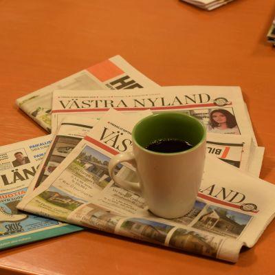 En kaffekopp och en hög med dagstidningar.