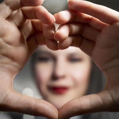 Ina Mikkola käsistä tehdyn sydämen läpi kuvattuna.