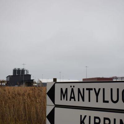 Porin Mäntyluodon kyltti, jonka taustalla Fortumin tuhkankäsittelylaitos.