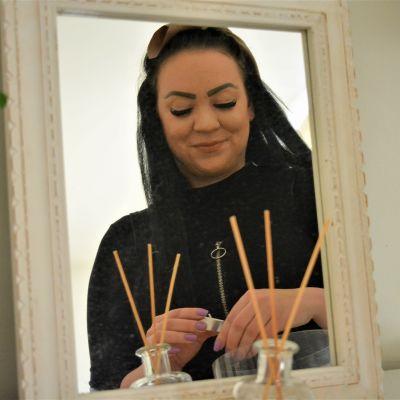 Nuori nainen Ina Virtanen sytyttää peilin edessä kynttilöitä.