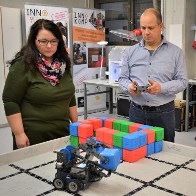 1. vuoden käsityönopettajaksi opiskeleva Heli Mäenpää ja 3. vuoden opiskelija Antti Vepsäläinen Rauman OKL:stä ohjaavat robottinosturia, jollaisia yläkoulun oppilaitakin opetetaan ohjelmoimaan.