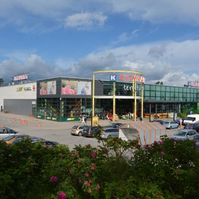 Bilar parkerade utanför en stor Citymarket-affär. Sommar.